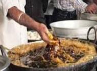 آشپزی که غذای در حال پخت را با دستش بهم هم میزند +عکس