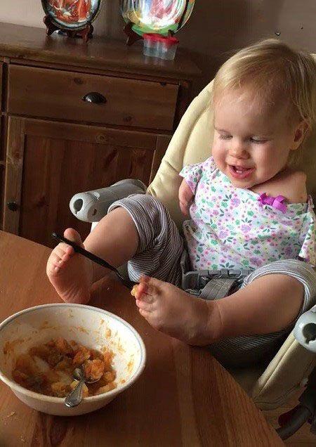 کودک بدون دستی که با پا غذا می خورد