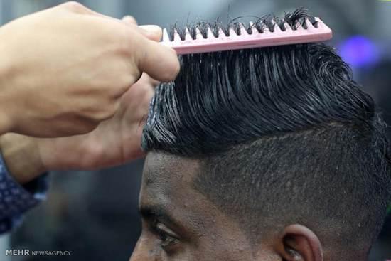 آرایشگری که با آتش موی سر را اصلاح می کند